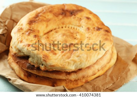 Flat bread on craft paper on wooden background
