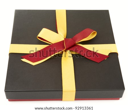 Flat cardboard gift box isolated on white, laces in spanish flag colors - stock photo