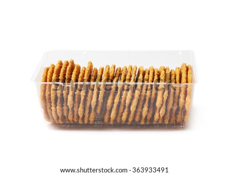 Flat cookies in a plastic case - stock photo