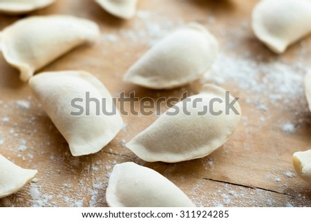 Flat dumplings sprinkled with flour on wooden surface. - stock photo