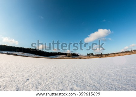 Flat frozen lake surface covered with fresh white snow for ice skating in fisheye vision - stock photo
