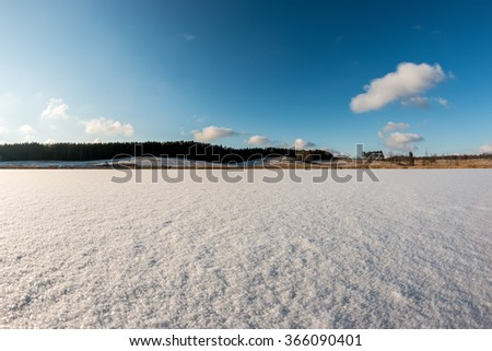 Flat frozen lake surface covered with white snow - stock photo