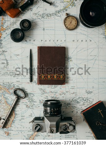 Flat lay adventure vintage gear for exploring or traveling on old map - stock photo