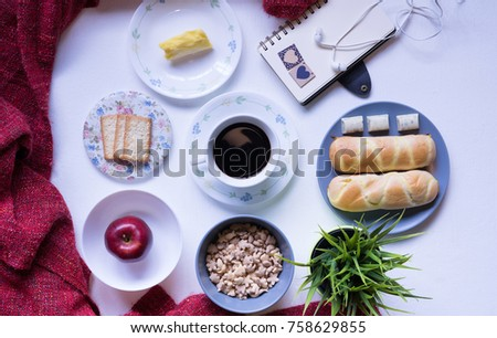 Flat Lay Breakfast table set up.Buns,Apple,Cereals,cupcake,butter and coffee with notebook and headphone on the white table.Lay Flat Food Photography.