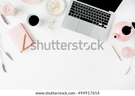 Flat lay fashion feminine home office workspace. Laptop, pink teapot, golden pen and clips. Top view