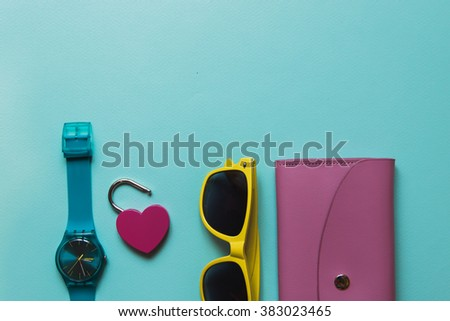 Flat lay fashion set: blue watch, pink purse and yellow sunglasses on blue background in pastel colors. Negative Space on top. - stock photo