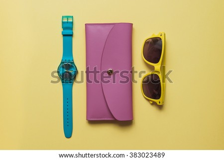 Flat lay fashion set: blue watch, pink purse and yellow sunglasses on yellow background in pastel colors - stock photo