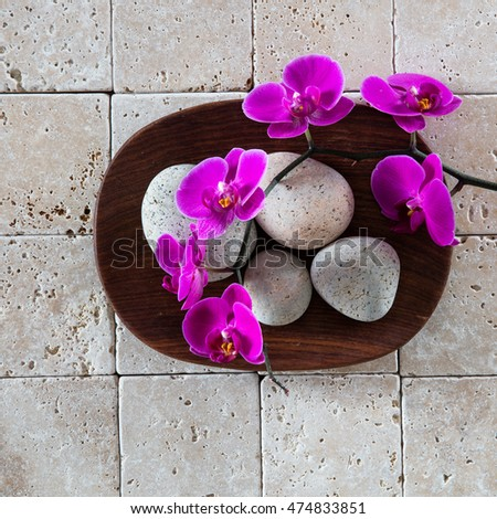 flat lay for minimal spa concept with beautiful round stones and pink orchids on a wooden tray and pure limestone background for natural beauty wallpaper