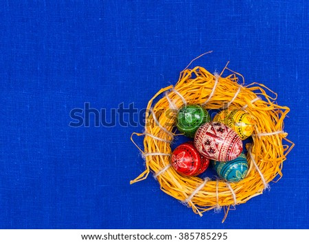 flat lay.greeting easter card with handmade easter eggs in nest in textile blue background - stock photo