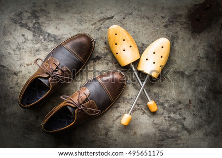 Flat lay, Men's leather shoes and wooden shoes trees on grunge rusty metal background, Still life