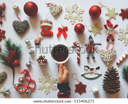 Flat lay of Christmas decoration ornaments on white background and woman hand holding cup of tea - Trendy minimal flat lay design