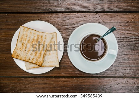 Flat lay of coffee and bread on wooden table.