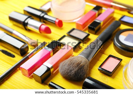 Flat lay of makeup cosmetics on yellow background
