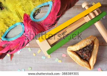 Flat lay of Purim Jewish holiday food and objects: hamantaschen, wooden Purim gragger and carnival mask. Copy text space. - stock photo