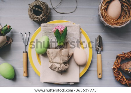 flat lay of table decorated for Easter with wrapped hyacinth flower, garden tools and colorful plate. Cozy home setting, Selective focus. - stock photo