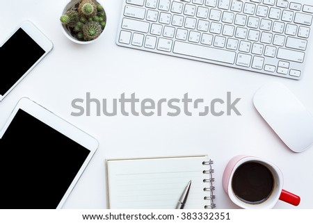 Flat lay photo of office desk with keyboard, notebook, tablet, smartphone and red cup, top view