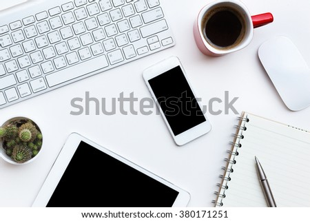 Flat lay photo of office desk with keyboard, tablet, smart phone and red cup, top view