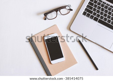 Flat lay photo of office desk with laptop, smartphone, eyeglasses and notebook with copy space background - stock photo