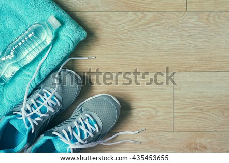 Flat lay photo of sports equipment sneakers,towel,bottle of water, top view, toned image over wooden background with copy space - stock photo