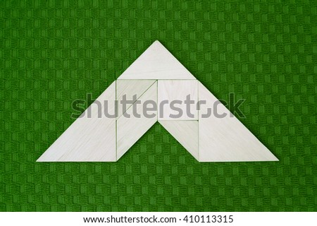 Flat lay - pictogram /symbol/ icon of roof, geometrical abstract background or arrow showing direction made of wooden tangram pieces. Unicolor background made of green fabric texture. Vignetting.  - stock photo