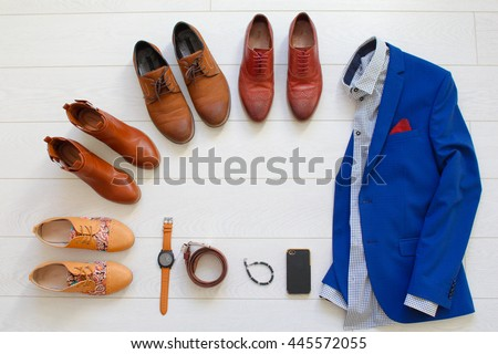 Flat lay set of brown shoes circled around men`s blue suit with shirt and some objects like watches, belt, bracelet and phone on white wooden background. Top view.
