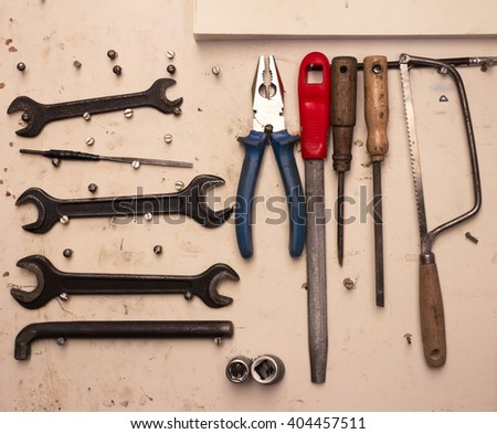 Flat lay - set of tools: pliers, screwdriver. saw, file, spanner. Real scene with lot of dirt  - stock photo