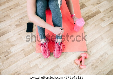 Flat lay sport photography. Female athlete  relax after workout. Fitness flat lay photography of  coach after training. Girl drinks healthy protein shake after workout.  - stock photo