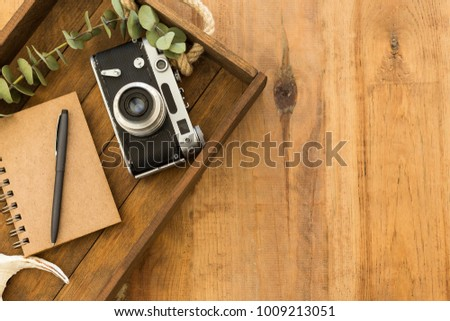 Flat lay with notepad, black pen and vintage film camera in wooden tray over rustic wooden tabletop. Copy space.