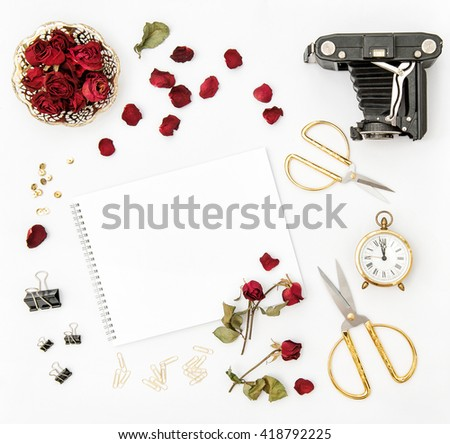 Flat lay with photo album, red rose petals, vintage camera, scissors on white background. Mock up sketchbook flowers. Minimalistic flat lay - stock photo
