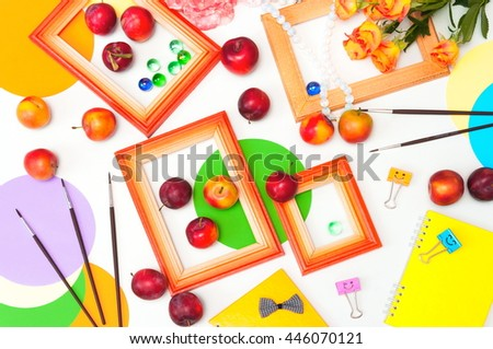 flat layout table, photo frame, brush, clips, rose, plum fruit, a beautiful composition on a white background, top view