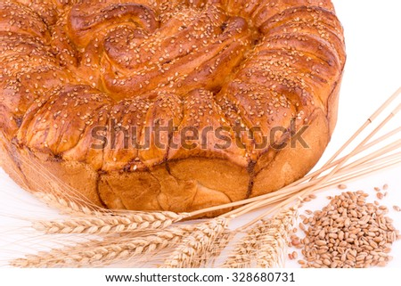 flat loaf isolated on a white background decorated with wheat stalks and grains
