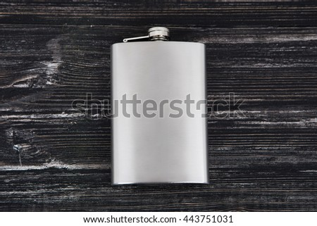 Flat metal flask and whiskey on wooden background