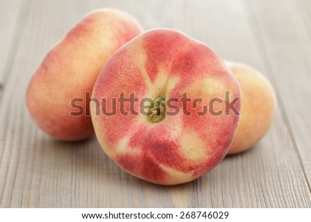 flat peaches on wood table - stock photo
