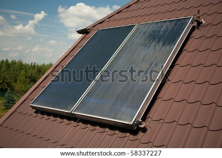 Flat-plate solar collector on roof in summer - stock photo