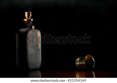 Flat scent bottle of frosted glass on a dark surface of the noble wood.