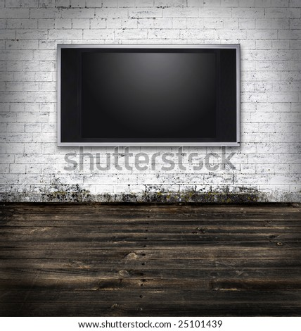 Flat screen television in a dark room with white bricks - stock photo