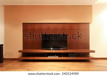 Flat screen TV at wooden shelf - stock photo