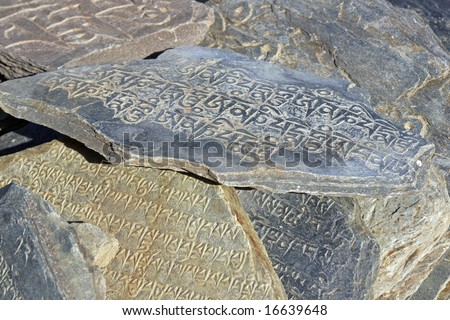 Flat stone carved with Buddhist Mantra.