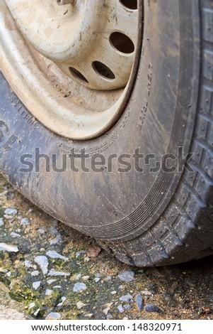 Flat  tire on car closeup shot of a flat tire of a car  - stock photo