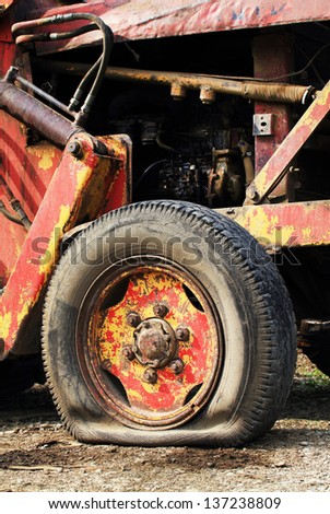 Flat tyre of a tractor - stock photo