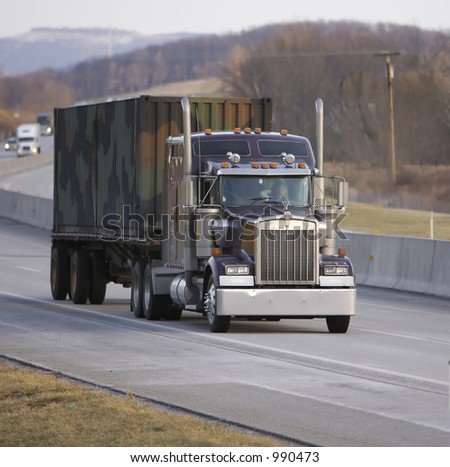 Flatbed Truck with Camo Cargo Container as Payload - stock photo