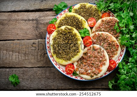 Flatbread with zaatar and meat(lahmacun) in ornament plate with parsley and tomatoes on wooden background. Arabian cuisine - stock photo