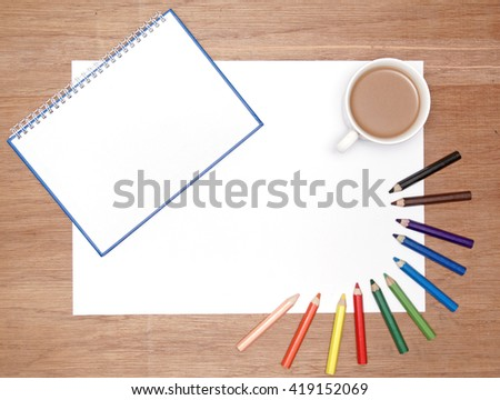 flatlaly of stationery. a spiral bound book, a blank white drawing paper, a cup of coffee and colouring pencil - stock photo