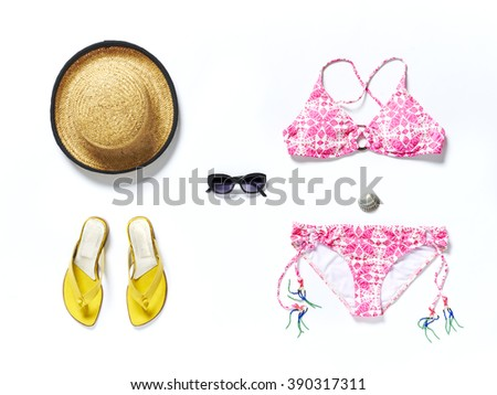 flatlay from above white beach with yellow sandals sunglasses bikini and straw hat - stock photo