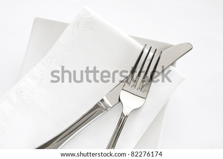 Flatware setting of a fork, knife and white napkin on a white plate against a white background. - stock photo