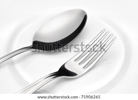 Flatware. Spoon and fork on a plate - stock photo