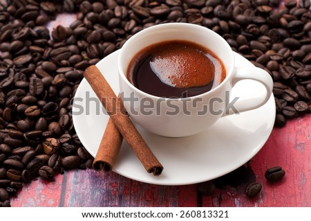Flavored coffee in the cup with cinnamon, standing on a wooden table in the coffee beans - stock photo