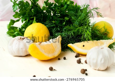 flavourings for cooking meat. slices of lemon, garlic cloves and parsley on white background - stock photo
