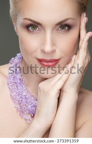 Flawless face. Vertical closeup of a gorgeous mature woman wearing necklace posing with her hands to her face smiling joyfully - stock photo