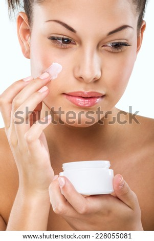 Flawless-skinned woman with moisturizing face cream  - stock photo